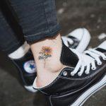 Tatuaggio Felicita e Gioia Simbolo girasole tatuato sulla caviglia