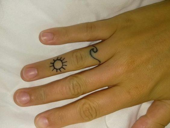 Piccolo tatuaggio sul dito onda con sole